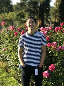 Kouta Lee standing outside in front of roses. Hands are in pockets.