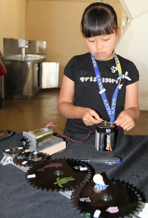 A girl readies the power supply for her gears