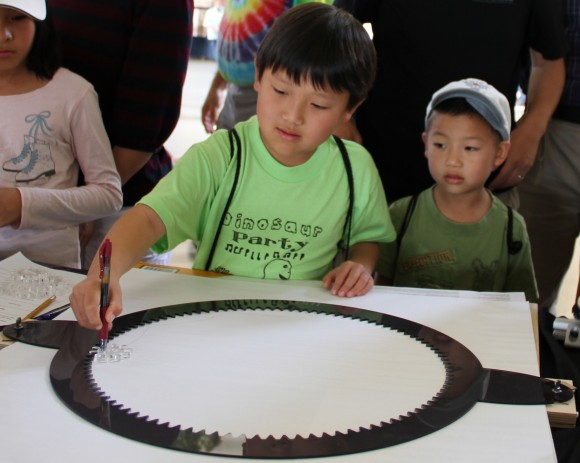 A boy rounds the spirograph track with the 10-tooth gear. The track and gears were cut with the laser cutter at the Mathematics Technology Lab.