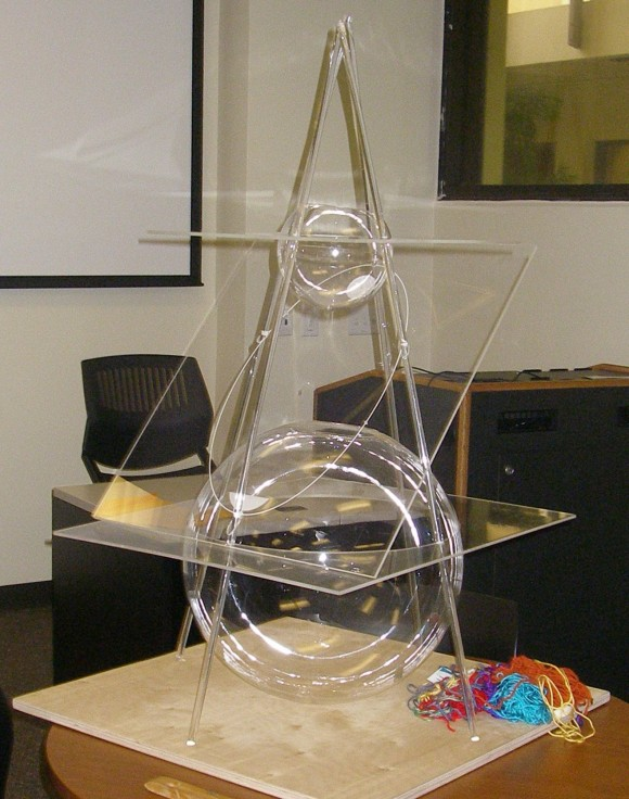 intersecting planes sculpture. the four poles suggest outline of cone. two spheres are tangent to intersecting planes sculpture l